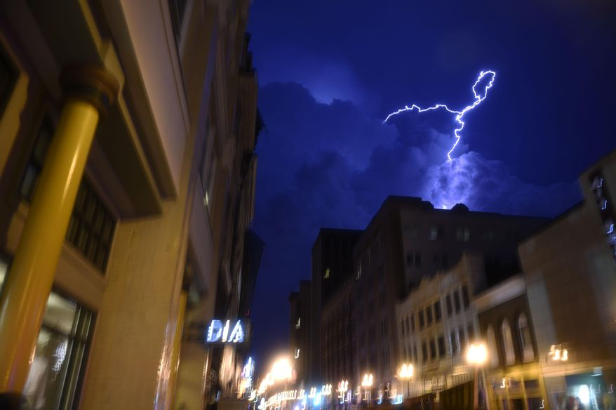 Lightning strikes over downtown in Knoxville, Tenn., on Sunday, July 27, 2014. Authorities say powerful storms crossing east Tennessee have destroyed 10 homes and damaged others, though there are no immediate reports of any deaths or injuries. (AP Photo/The Knoxville News Sentinel, Saul Young)