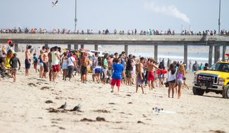 Pedestrians and beachgoers stand on the shore near Venice Beach as lifeguards, right, bring in a swimmer rescued from the water after a lightening strike Sunday, July 27, 2014, in Los Angeles. (AP Photo/Steve Christenesn)
