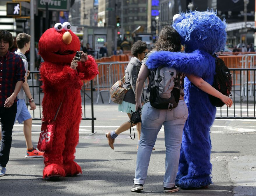 An Elmo character (left) uses a woman's camera to photographer her with a Cookie Monster character in New York's Times Square. A man in a Spider-Man costume was charged with assaulting a police officer after insisting on larger payment from a tourist.  (Associated Press)