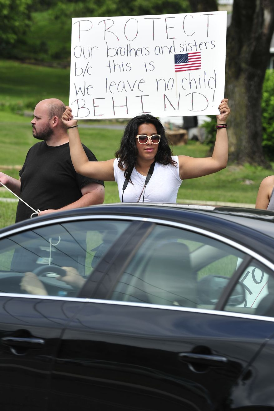 Angel Diaz of Easton, PA holds a protest sign as traffic passes by. Members of the Industrial Workers of the World Lehigh Valley branch rally outside the KidsPeace Broadway campus, Sunday, July 27, 2014 in Fountain Hill, Pa. in support of the unaccompanied immigrant children who are temporarily housed there. (AP Photo/Chris Post)