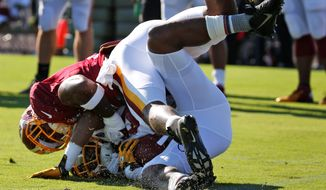 Redskins receiver Rashad Ross (bottom) is tackled by safety Akeem Davis during the first practice in full pads on Monday at the Bon Secours Training Center in Richmond.