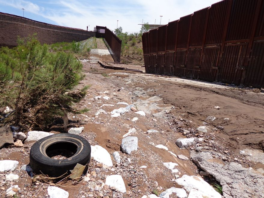 A section of fence lies collapsed just west of the Mariposa Port of Entry in Nogales, Ariz., Sunday, July 27, 2014, after severe storms in southern Arizona over the weekend knocked down a chunk of the metal border fence that divides Mexico and the U.S. Rain runoff from the storms destroyed about 60 feet worth of fence and caused damage to homes just north of it. (AP Photo/Nogales International, Jonathan Clark)