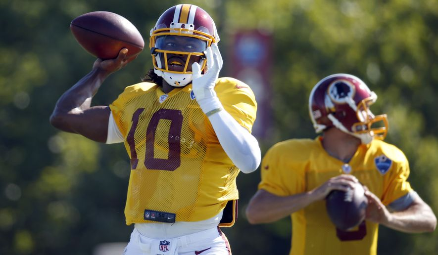 Washington Redskins quarterbacks Robert Griffin III and Kirk Cousins look to pass during practice at the team's NFL football training facility, Monday, July 28, 2014 in Richmond, Va. (AP Photo/Alex Brandon)