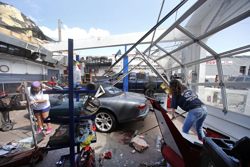 Master Auto manager Marie Annaloro, left, and Victoria Ohlson,right, sweep glass and debris in the service garage where the roof blew off in Revere, Mass. Monday, July 28, 2014, after a tornado touched down. Revere Deputy Fire Chief Mike Viviano says the fire department in that coastal city has received dozens of calls reporting partial building and roof collapses, and downed trees and power lines. Viviano says there are no immediate reports of deaths or serious injuries. (AP Photo/Elise Amendola)
