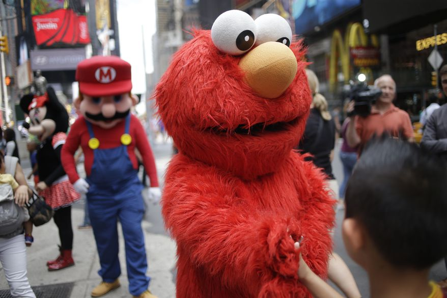 ** FILE ** A person dressed as Elmo shakes hands with a pedestrian in Times Square on Monday, July 28, 2014, in New York. New York City Mayor Bill de Blasio said Monday that he believes the people wearing character costumes in Times Square should be licensed and regulated. (AP Photo/Seth Wenig)