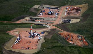 This June 12, 2014, aerial photo shows four oil wells in various stages of production, from drilling to a fully functional pump producing well, in McKenzie County, N.D. An oil boom near North Dakota's Badlands has created an infrastructure building frenzy as the rush for jobs and oil production demand roads, homes, food trucks, stores and more. (AP Photo/Charles Rex Arbogast)