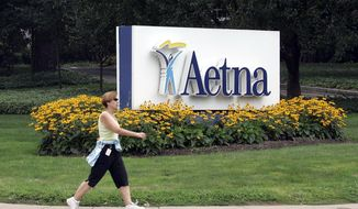 A woman strides past the Hartford, Conn., headquarters of Aetna Inc. in this July 31, 2008, file photo. (AP Photo/Bob Child, File)