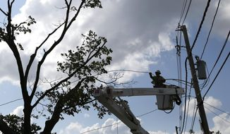 A National Grid crew member works to restore power on lines in Revere, Mass. Monday, July 28, 2014, after a tornado touched down. Revere Deputy Fire Chief Mike Viviano says the fire department in that coastal city has received dozens of calls reporting partial building and roof collapses, and downed trees and power lines. Viviano says there are no immediate reports of deaths or serious injuries. (AP Photo/Elise Amendola)