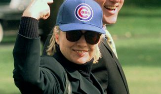 First lady Hillary Rodham Clinton points to her Chicago Cubs baseball cap as she and President Clinton leave the White House Saturday, Oct. 3, 1998 on their way to Camp David. (AP Photo/Wilfredo Lee)