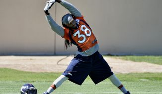 In this Wednesday, May 28, 2014 photo, Denver Broncos' Quinton Carter stretches during an NFL football organized team activity, in Englewood, Colo. Carter, who was on injured reserve last season, is back and turning heads at training camp. (AP Photo/Jack Dempsey)
