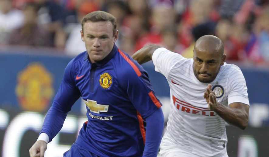 Manchester United's Wayne Rooney, front moves the ball as Inter Milan's Jonathan, right, defends during the first half of a soccer game at  the 2014 Guinness International Champions Cup, Tuesday, July 29, 2014, in Landover, Md.  Manchester United won 5-3 in a penalty shootout. (AP Photo/Luis M. Alvarez)