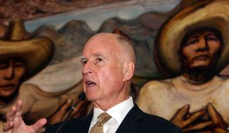 Back-dropped by a mural by Mexican painter David Alfaro Siqueiros, California Gov. Jerry Brown speaks during a press conference with U.S. Ambassador to Mexico Anthony Wayne, not seen, at the Soumaya museum in Mexico City, Monday, July 28, 2014. (AP Photo/Marco Ugarte)