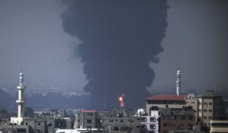 Seen from Gaza City, smoke and flames rise from Gaza's electricity distribution company plant after it was hit by Israeli strikes in the Nusseirat refugee camp, central Gaza Strip,Tuesday, July 29, 2014. Hours after Gaza's only power plant was hit, a tall column of thick black smoke continued to rise from a burning fuel tank there. The plant's shutdown was bound to lead to further serious disruptions of the flow of electricity and water to Gaza's 1.7 million people. (AP Photo/Lefteris Pitarakis)