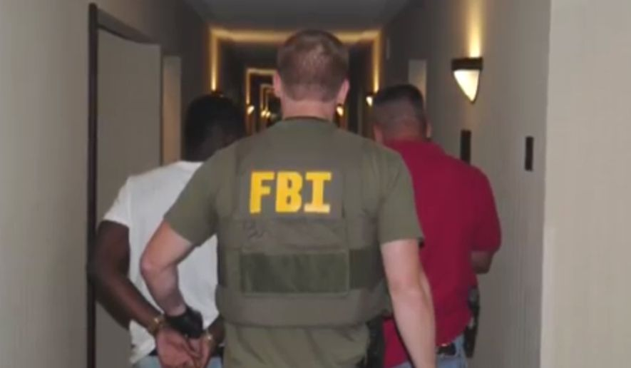 ** FILE ** In this June 2014 image from video provided by the FBI, authorities raid a hotel in Jackson, Mississippi.  When FBI agents and police officers fanned out across the country last month in a weeklong effort to rescue child sex trafficking victims, they pulled kids as young as 11 from dingy motel rooms, truck stops and homes. (AP Photo/FBI)
