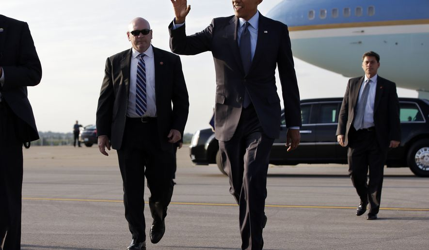 President Barack Obama waves to people waiting as he arrives at Kansas City International Airport in Kansas City, Mo., Tuesday, July 29, 2014. (AP Photo/Jacquelyn Martin)