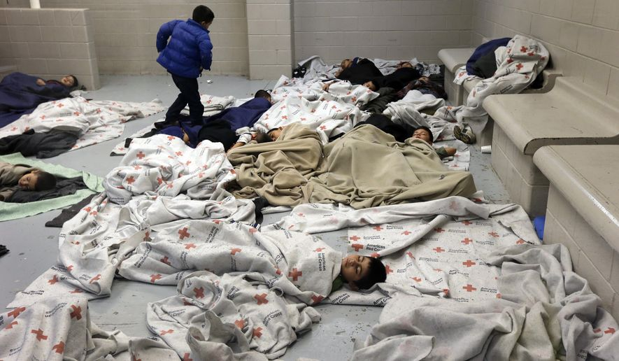 ** FILE ** In this June 18, 2014, file photo, detainees sleep in a holding cell at a U.S. Customs and Border Protection processing facility in Brownsville, Texas. (AP Photo/Eric Gay, Pool)