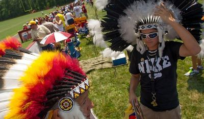 Carlos Rodriguez, left, and his nephew Josh Holmes, 15, of Dumfries, Va., wear headdresses as they wait for practice to begin on the first day of training camp at Redskins Park, Ashburn, Va., Thursday, July 26, 2012. (Andrew Harnik/The Washington Times)