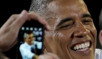 A guest uses their cellphone to photograph President Barack Obama as greets the crowd after speaking about the economy, Wednesday, July 30, 2014, at the Uptown Theater in Kansas City, Mo. (AP Photo/Charlie Riedel) ** FILE **