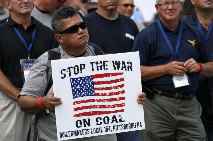 A member of the Boilermakers local 154 Pittsburgh holds a sign at a rally to support American energy and jobs in the coal and related industries at Highmark Stadium in downtown Pittsburgh, Wednesday, July 30, 2014. The rally is being held the day before the Environmental Protection Agency conducts public hearings on its new emissions regulations for existing coal fired power plants. (AP Photo/Gene J. Puskar)
