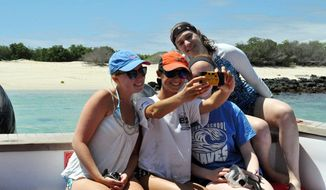 Four vacationers on holiday record the moment with a selfie in this file photo. (AP Photo Jacqui Whitt) **FILE**