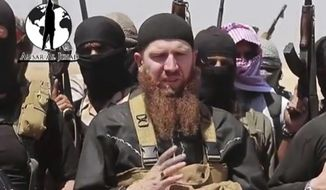 Omar al-Shishani stands next to a group of ISIL fighters as they declare the elimination of the border between Iraq and Syria, June 28, 2014. (AP Photo/militant social media account via AP video)
