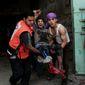 Palestinians help carry an injured man to an ambulance following an Israeli Strike in Shijaiyah neighborhood, eastern Gaza City, Wednesday, July 30, 2014. (AP Photo/Adel Hana)