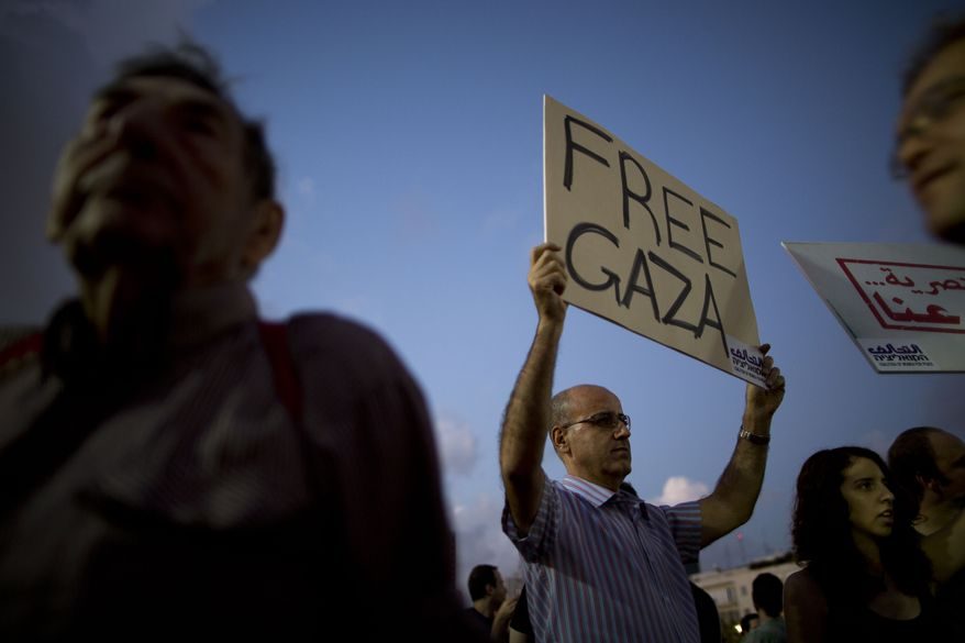 FILE - In this file photo taken Saturday, July 19, 2014, an Israeli left-wing activist holds a sign during a demonstration against Israel's operation in the Gaza Strip, in Tel Aviv, Israel. Despite Israeli casualties and world criticism, a near-consensus in Israel supports the government's conduct of the Gaza war, views Hamas as the aggressor and considers outsiders' moralizing as hypocritical, ignorant or both. A small but vocal opposition exists, but those arguing for peace are vociferously shouted down in a way rarely seen in a country long proud of its spirited, democratic debate. (AP Photo/Oded Balilty, File)