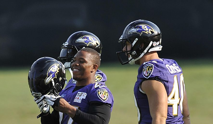 Baltimore Ravens running back Ray Rice, left, smiles as he puts on his helmet next to Shaun Chapus, right, during NFL football training camp practice, Thursday, July 31, 2014, in Owings Mills, Md.(AP Photo/Gail Burton)