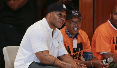 Actor and music artist L.L. Cool J, left, talks with Def Jam co-founder Russell Simmons on a visit to speak with youth at the juvenile detention center of Rikers Island, Thursday, July 31, 2014, in New York. Simmons, founder of the RushCard Keep the Peace initiative, was accompanied by L.L. Cool J to the detention center to offer advice to the inmates on reducing violence in their neighborhoods. (AP Photo/Julie Jacobson)