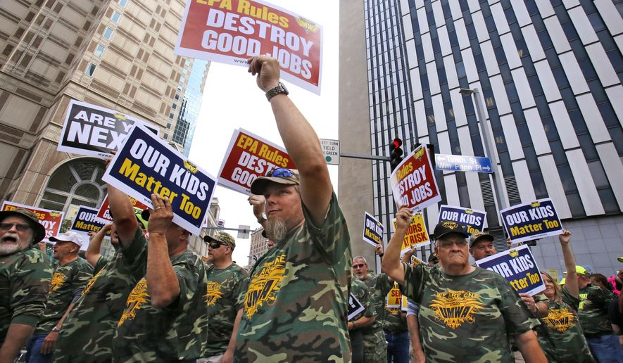 Some 5000 union members, led by the United Mine Workers of America, march outside the William S. Moorhead Federal Building, right rear, Thursday, July 31, 2014. Thursday is the first of two days of public hearings being held by the Environmental Protection Agency in Pittsburgh to discuss stricter pollution rules for coal-burning power plants proposed by the EPA.(AP Photo/Gene J. Puskar)