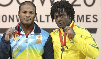 In this image taken Sunday July 27, 2014 Australia's Francois Etoundi  bronze medal winner, left, stands on the podium with gold medal winner India's Sathish Sivalingam following the men's 77kg weightlifting final at the Commonwealth Games Glasgow 2014  in Glasgow Scotland.  Etoundi,  was stripped of his games accreditation Thursday July 31, 2014  after being arrested over an alleged assault during an altercation in the athletes' village in Glasgow.  (AP Photo/Dominic Lipinski/PA)   UNITED KINGDOM OUT
