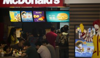 People dine at a McDonald's restaurant as a display board, top right, shows Filet-O-Fish burger available in Beijing, China Thursday, July 31, 2014. Global fast food chains are rushing to expand in China but even experienced operators face costly pitfalls in a fast-changing food supply industry plagued by repeated safety scandals. (AP Photo/Andy Wong)