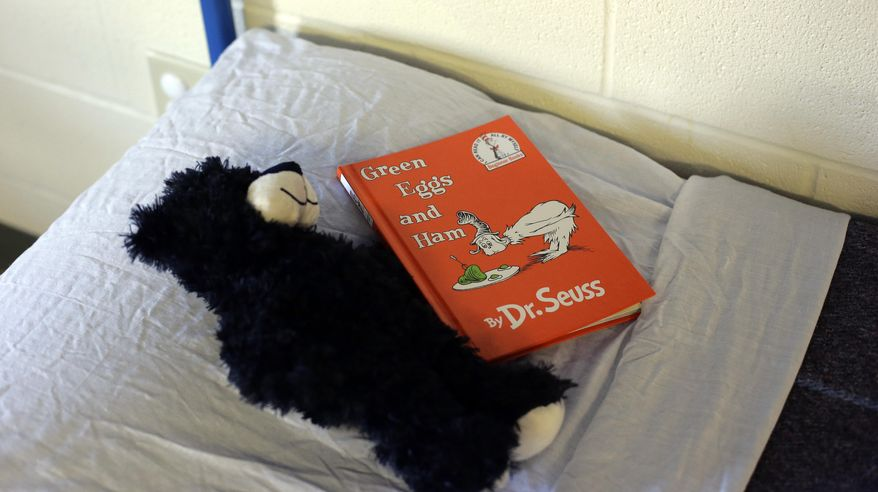 A stuffed bear and children's book sit on a child's bed the Karnes County Residential Center in Karnes City, Texas on Thursday, July 31, 2014. Federal officials gave a tour of the South Texas immigration detention facility that has been retooled to house adults with children who have been apprehended at the border. (AP Photo/Eric Gay)