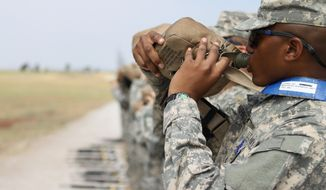 Pfc. Destavius Washington drinks water from his 2-quart canteen while at the zero range with the 1st Battalion, 79th Field Artillery. (U.S. Army photo)