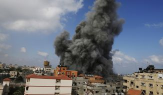 Smoke rises after an Israeli strike hit the offices of the Hamas movement's Al-Aqsa satellite TV station, in Gaza City, northern Gaza Strip, Thursday, July 31, 2014. Israel said Thursday it has called up another 16,000 reservists, allowing it to potentially widen its Gaza operation against the territory's Hamas rulers in a war that has killed more than 1,300 Palestinians and more than 50 Israelis. (AP Photo/Hatem Moussa)