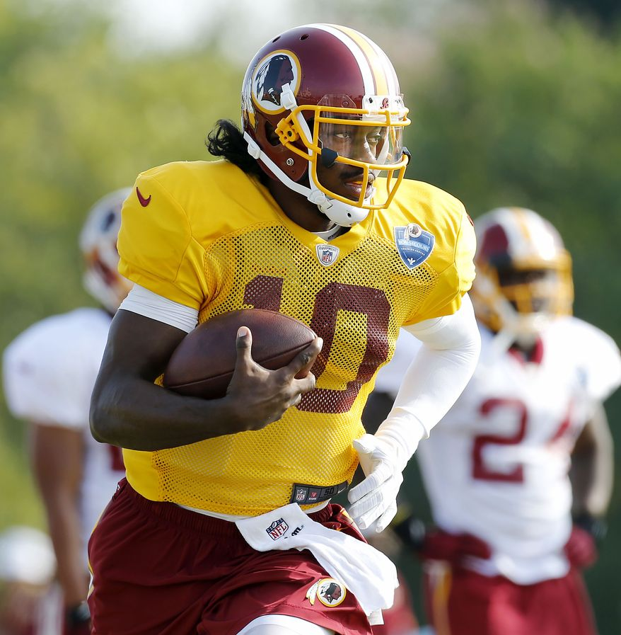 Washington Redskins' Robert Griffin III runs with the ball during morning practice at the Redskins training center in Richmond Va., Thursday, July 31, 2014. (AP Photo/Richmond Times-Dispatch,Mark Gormus)