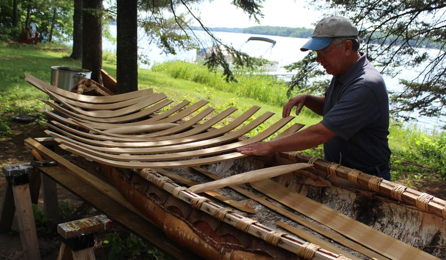 ADVANCE FOR MONDAY, AUG. 4 - David Gunelson, of Pengilly, Minn., who has built and restored about 10 wooden boats, works on a birch bark canoe July 24, 2014, in Pengilly. (AP Photo/The Daily Tribune, Tony Potter)