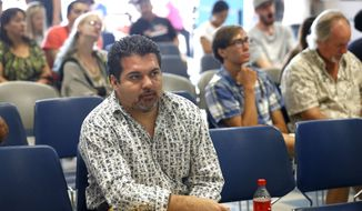 Immigrant and longtime resident in the United States Joel Acosta waits to be processed for his permanent driver's license, at a Department of Motor Vehicles office, in Denver, Friday Aug. 1, 2014. Colorado began issuing driver's licenses and identification cards on Aug. 1, 2014 to immigrants who are in the country, regardless of legal immigration status. (AP Photo/Brennan Linsley)