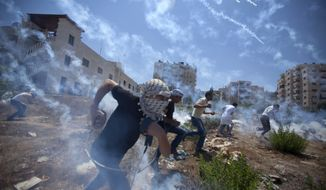 Palestinians run for cover during clashes with Israeli soldiers following a protest against the war in the Gaza Strip, outside Ofer, an Israeli military prison near the West Bank city of Ramallah, Friday, Aug. 1, 2014. (AP Photo/Majdi Mohammed)