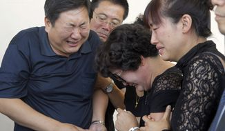 The  parents of slain USC graduate student Xinran Ji, father Songbo Ji, left and mother, Du Jinhui, second from right, sob after viewing the body of Xinran, along with other unidentified family members at an Alhambra, Calif., funeral home, Thursday, July 31, 2014. Four U.S. teens were charged Tuesday with murder in the fatal beating of Chinese graduate student, Xinran, with a baseball bat and wrench as he walked to his apartment. (AP Photo/ Nick Ut)