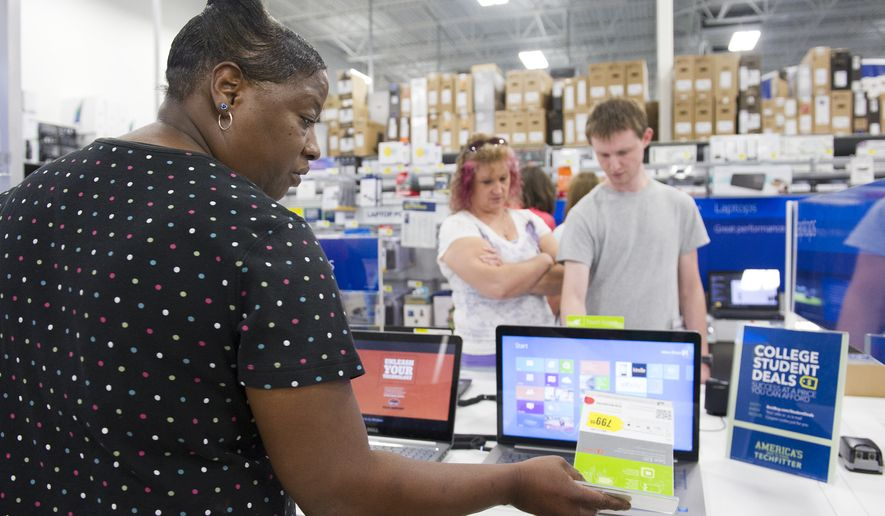 Deborah Simmons looks at the price tag of a laptop computer as she shops with her 14-year-old son Carlos Simmons during a sales tax holiday sale at Best Buy on Friday, August 1, 2014 in Augusta, Ga. Officials said state and local sales taxes in most Georgia counties will be waived between Aug. 1 and 2. (AP Photo/The Augusta Chronicle, Sara Caldwell)