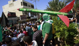 A supporter of Hamas holds a representation of a rocket as others shout slogans against the Israeli attack on the Gaza Strip, during a protest in the West Bank town of Tulkarem town on Friday, Aug. 1, 2014. A Palestinian man was shot and killed during clashes with Israeli troops near Tulkarem, Palestinian security sources said. (AP Photo/Mohammed Ballas)
