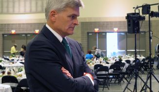 Republican U.S. Rep. Bill Cassidy speaks to a local elected official about his campaign for Louisiana's U.S. Senate seat after talking at the Louisiana Municipal Association's annual convention on Saturday, Aug. 2, 2014, in Baton Rouge, La. Cassidy is running against three-term Democratic incumbent Sen. Mary Landrieu. (AP Photo/Melinda Deslatte)