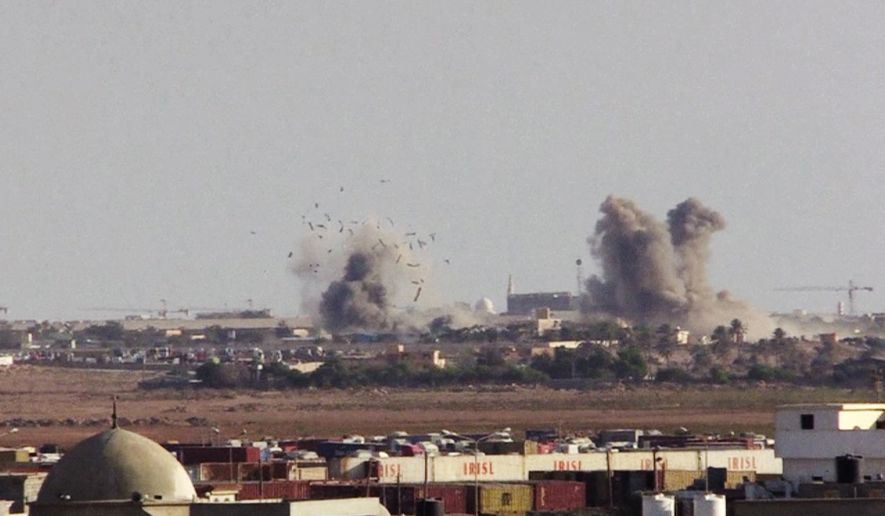 In this image made from AP video on Friday, Aug. 1, 2014, plumes of smoke and debris rise from a base of Islamic militias after a MiG fighter jet's strike in Benghazi, Libya. MiG fighter jets, reportedly under the control of renegade general, Khalifa Hifter, struck in retaliation the bases of Islamic militias in Benghazi on Friday, as a coalition of Islamic militias over the past week captured a number of army bases in Benghazi, driving out troops and police and seizing large weapon stores. (AP Photo/AP video)
