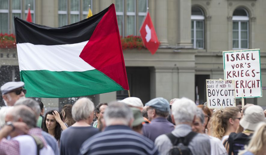**FILE** Protesters hold up banners and Palestinian flags during a protest against Israel and to show solidarity to the people in the Gaza strip, at the Bundesplatz square  in Bern, Switzerland, Saturday, Aug.  2, 2014. Poster at right reads : Israel to a War Tribunal.   (AP Photo/Keystone,Peter Klaunzer)