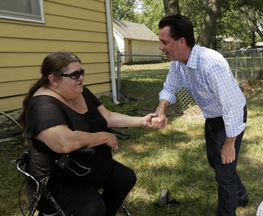 Milton Wolf, right, a Republican candidate for the U.S. Senate in Kansas, talks to a woman as he campaigns at a parade on Saturday in Gardner, Kan. Backed by the tea party, Mr. Wolf is challenging incumbent Pat Roberts in the primary election Tuesday, Aug. 5. (AP Photo/Charlie Riedel)