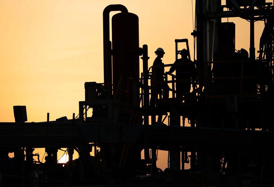 Oil men work on a new oil rig at sunset in the desert oil fields of Sakhir, Bahrain, Sunday, Aug. 3, 2014. (AP Photo/Hasan Jamali)