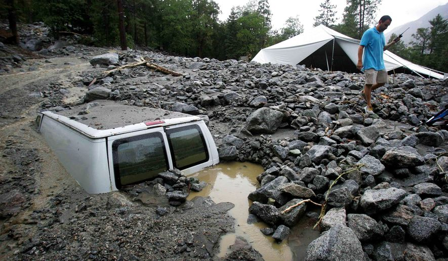 An official of Forest Home Christian Conference Center in Forest Falls, Calif., inspects damage on the property following thunderstorms on Sunday, Aug. 3, 2014. About 1,500 residents of Oak Glen, and another 1,000 residents of Forest Falls in the San Bernardino Mountains were unable to get out because the roads were covered with mud, rock and debris, authorities said. (AP Photo/The Press-Enterprise, David Bauman)