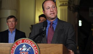 In this file Aug. 4, 2014 photo, U.S. Rep. Jared Polis, D-Colo., takes questions during a news conference about fracking, as Colo. Gov. John Hickenlooper, left, stands at left, inside the Capitol, in Denver. (AP Photo/Brennan Linsley, file)