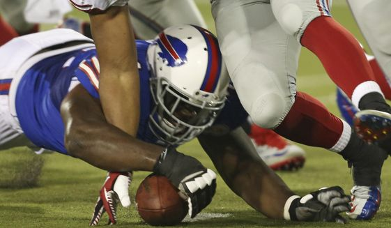 Buffalo Bills offensive tackle Cyrus Kouandjio (71) recovers a fumble under pressure from New York Giants defensive end Kerry Wynn (69) during the fourth quarter at the Pro Football Hall of Fame exhibition NFL football game Sunday, Aug. 3, 2014, in Canton, Ohio. The Giant defeated the Bills 17-13. (AP Photo/Ron Schwane) **FILE**